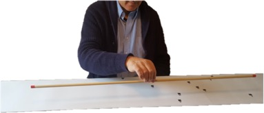A man lifting a balanced wooden rod using his forefinger and thumb.