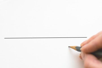 A person using a pencil to mark the middle of a thin line on a piece of paper.