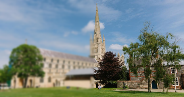 A photograph of Norwich cathedral, left half blurred and the right half in focus.